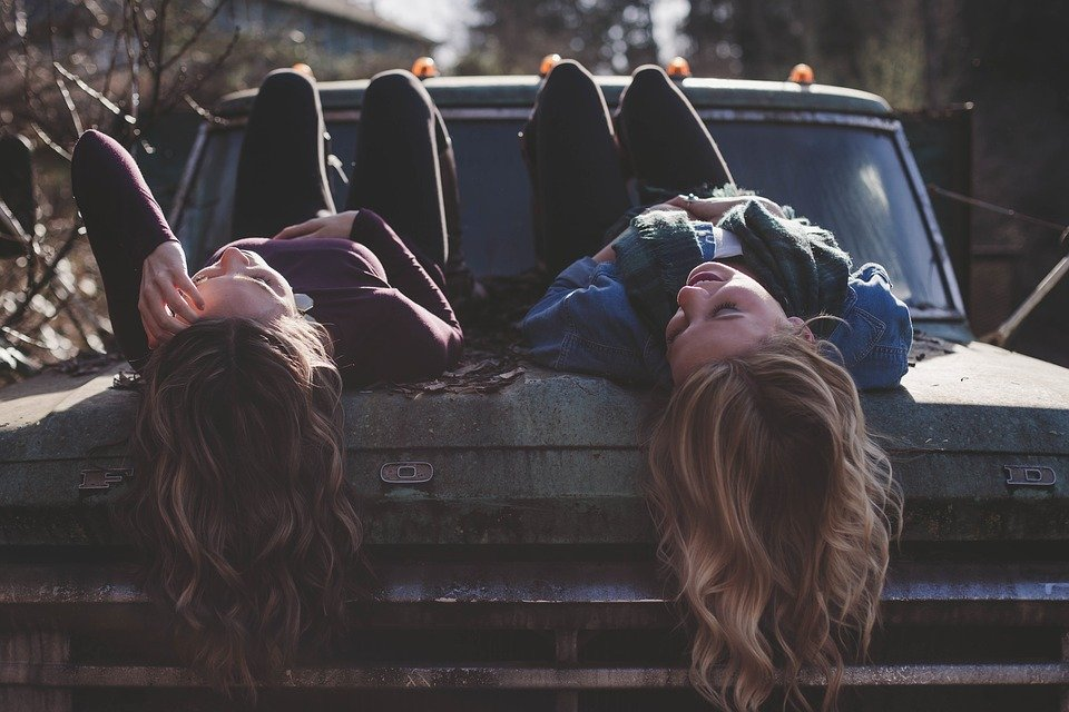 Surprise and old friend by chilling at your old hangout spot like these two girls hanging out on a parked truck.